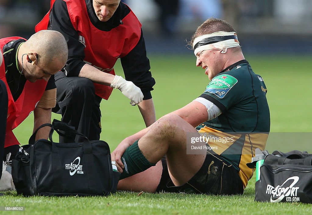 Dylan Hartley of Northampton receives attention to an injured ankle during the Heineken Cup pool 1 match between Northampton Saints and Ospreys at Franklin's Gardens on October 20, 2013 in Northampton, England.