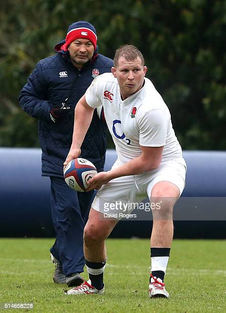 Dylan Hartley the England captain passes the ball watched by head coach Eddie Jones during the England training session held at Pennyhill Park on...