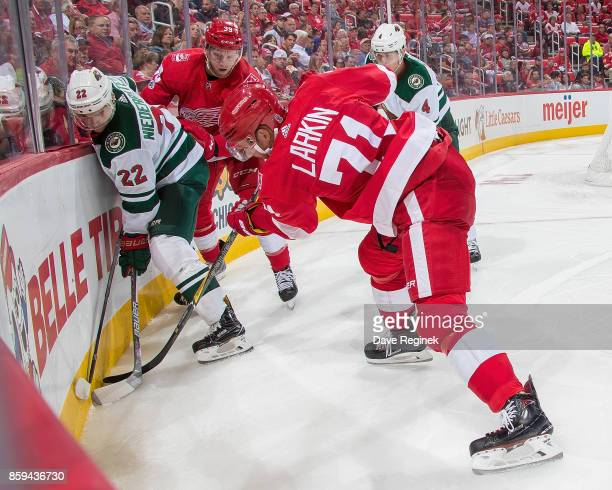 Dylan Larkin and Anthony Mantha of the Detroit Red Wings battles along the boards with Nino Niederreiter and Mike Reilly of the Minnesota Wild during...