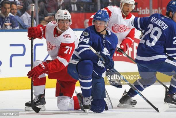 Dylan Larkin of the Detroit Red Wings battles against Auston Matthews of the Toronto Maple Leafs in an NHL game at the Air Canada Centre on October...