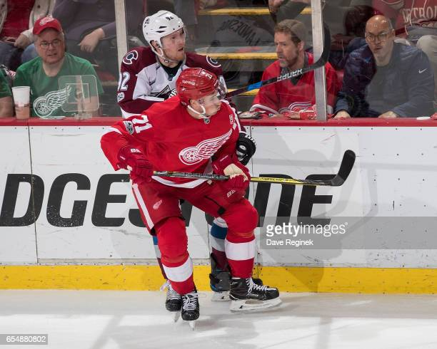Dylan Larkin of the Detroit Red Wings battles for position along the boards with Gabriel Landeskog of the Colorado Avalanche during an NHL game at...