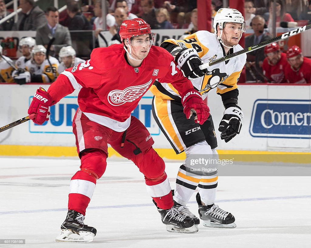 Dylan Larkin #71 of the Detroit Red Wings battles for position with Tom Kuhnhackl #34 of the Pittsburgh Penguins during an NHL game at Joe Louis Arena on January 14, 2017 in Detroit, Michigan.