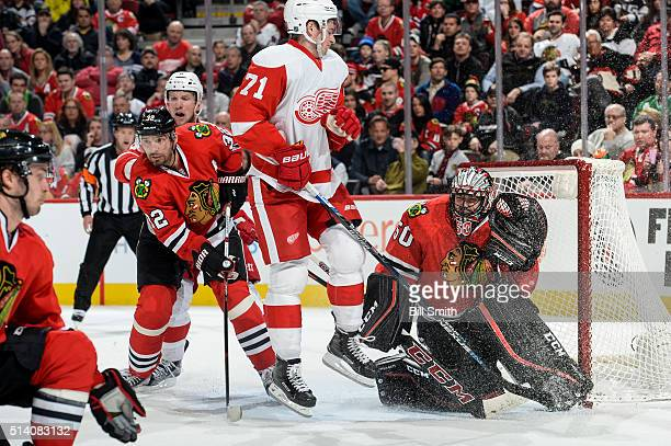 Dylan Larkin of the Detroit Red Wings jumps in front of goalie Corey Crawford of the Chicago Blackhawks as Michal Rozsival and Justin Abdelkader...