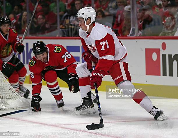 Dylan Larkin of the Detroit Red Wings moves under pressure from Lubomir Visnovsky of the Chicago Blackhawks during a preseason game at the United...