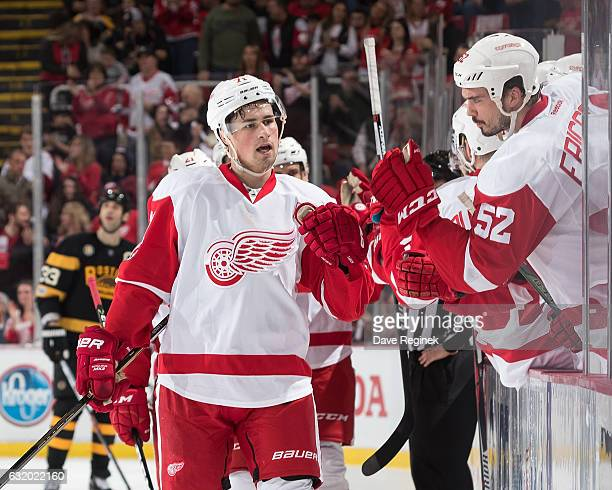 Dylan Larkin of the Detroit Red Wings pounds gloves with teammate Jonathan Ericsson following his first period goal during an NHL game against the...