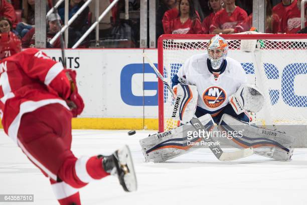 Dylan Larkin of the Detroit Red Wings shoots the puck on goaltender Thomas Greiss of the New York Islanders during an NHL game at Joe Louis Arena on...
