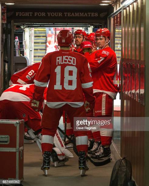 Dylan Larkin of the Detroit Red Wings waits outside the locker room with teammates Robbie Russo and Drew Miller prior to warmups before an NHL game...