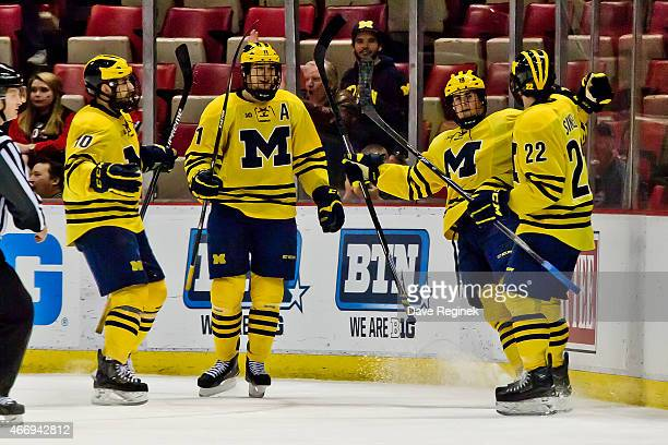 Dylan Larkin of the Michigan Wolverines celebrates his third period goal with teammates Andrew Sinelli Zach Hyman and Justin Selman against Wisconsin...