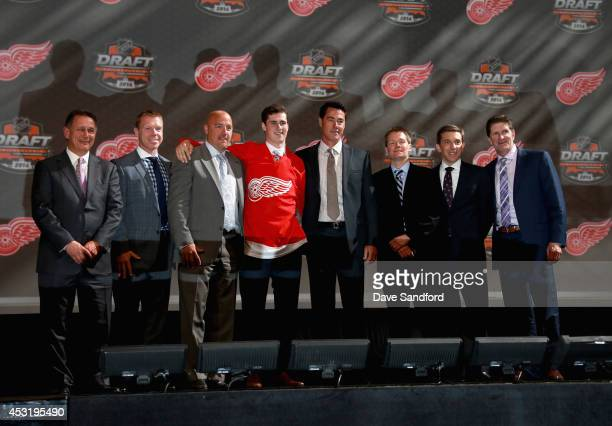 Dylan Larkin stands with team personnel after being selected 15th overall by the Detroit Red Wings during the 2014 NHL Entry Draft at Wells Fargo...