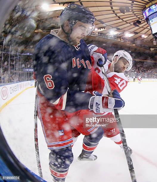 Dylan McIlrath of the New York Rangers is checked by Henrik Zetterberg of the Detroit Red Wings during the first period at Madison Square Garden on...