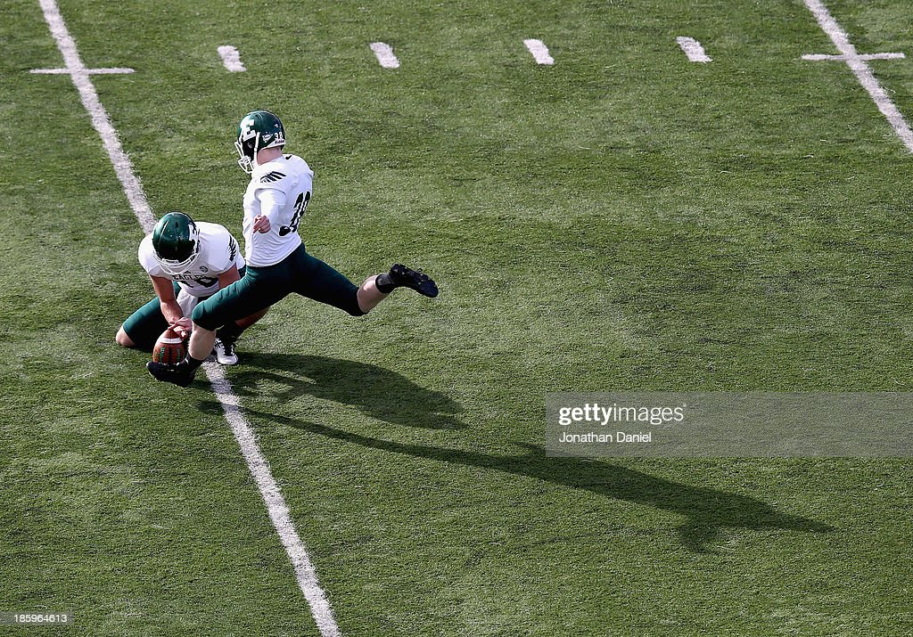 Dylan Mulder #38 of the Eastern Michigan Eagles kicks a field goal out of the hold of Mark Iannotti #10 against the Northern Illinois Huskies at Brigham Field on October 26, 2013 in DeKalb, Illinois. Northern Illinois defeated Eastern Michigan 59-20.