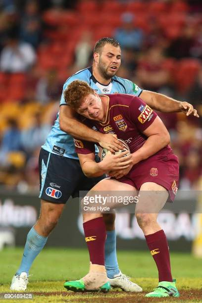Dylan Napa of the Maroons is tackled by Wade Graham of the Blues during game one of the State Of Origin series between the Queensland Maroons and the...