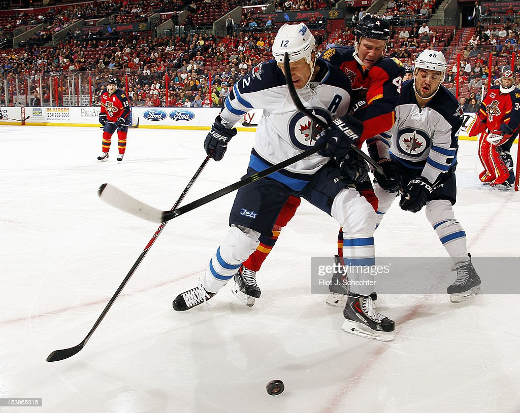 <a gi-track='captionPersonalityLinkClicked' href=/galleries/search?phrase=Dylan+Olsen&family=editorial&specificpeople=5894613 ng-click='$event.stopPropagation()'>Dylan Olsen</a> #4 of the Florida Panthers fights for possession against <a gi-track='captionPersonalityLinkClicked' href=/galleries/search?phrase=Olli+Jokinen&family=editorial&specificpeople=202946 ng-click='$event.stopPropagation()'>Olli Jokinen</a> #12 and teammate <a gi-track='captionPersonalityLinkClicked' href=/galleries/search?phrase=Devin+Setoguchi&family=editorial&specificpeople=2221039 ng-click='$event.stopPropagation()'>Devin Setoguchi</a> #40 of the Winnipeg Jets at the BB&T Center on December 5, 2013 in Sunrise, Florida.