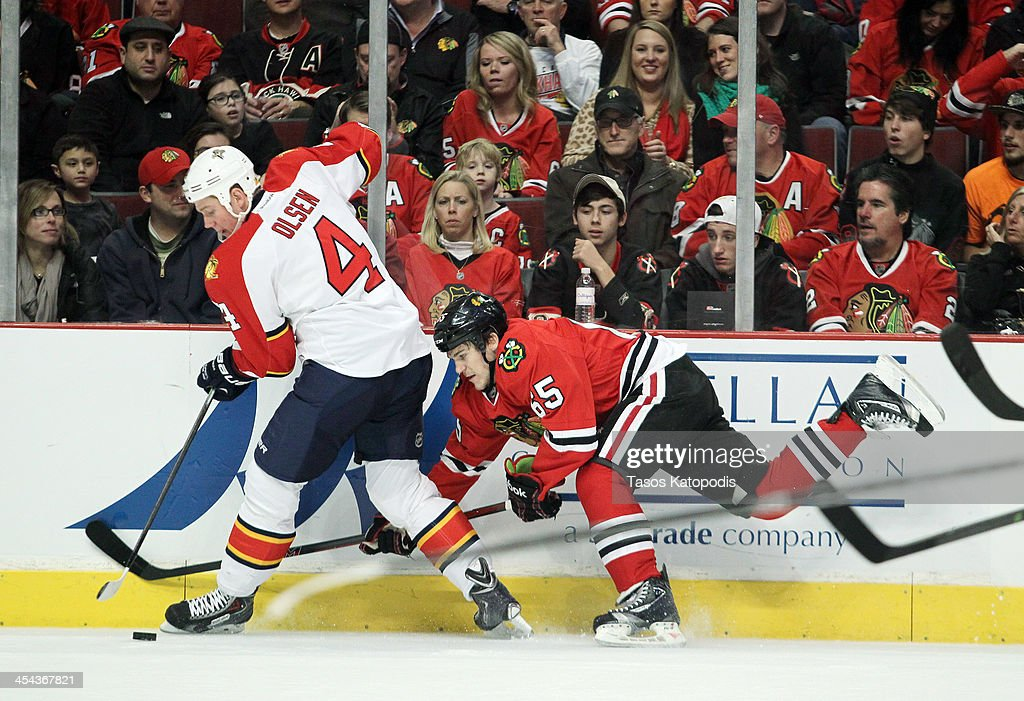 <a gi-track='captionPersonalityLinkClicked' href=/galleries/search?phrase=Dylan+Olsen&family=editorial&specificpeople=5894613 ng-click='$event.stopPropagation()'>Dylan Olsen</a> #4 of the Florida Panthers fights for the puck with Andrew Shaw #65 of the Chicago Blackhawks at the United Center on December 8, 2013 in Chicago, Illinois.