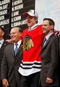 Dylan Olsen poses for a photo on the podium with General Manager Scottie Bowman left and another member of the Chicago Blackhawks organization after...