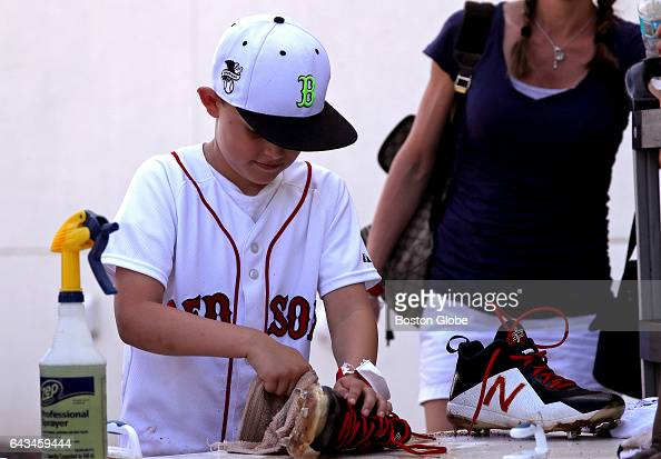 Dylan Pedroia takes a turn at cleaning his dad Dustin Pedroia's cleats after the day's workout on day six of Red Sox Spring Training at Jet Blue Park...
