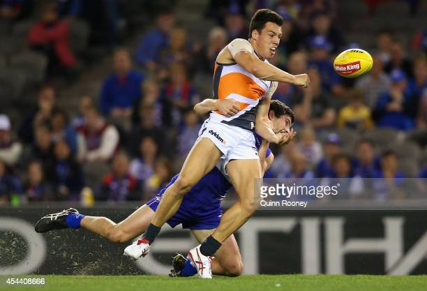 Dylan Shiel of the Giants handballs whilst being tackled by Tom Liberatore of the Bulldogs during the round 23 AFL match between the Western Bulldogs...
