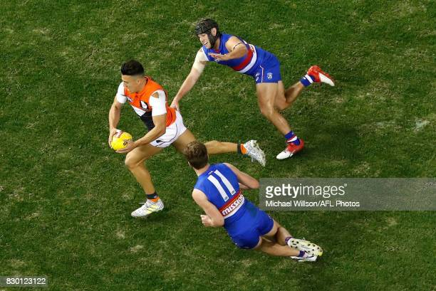 Dylan Shiel of the Giants is chased by Caleb Daniel of the Bulldogs and Jack Macrae of the Bulldogs during the 2017 AFL round 21 match between the...