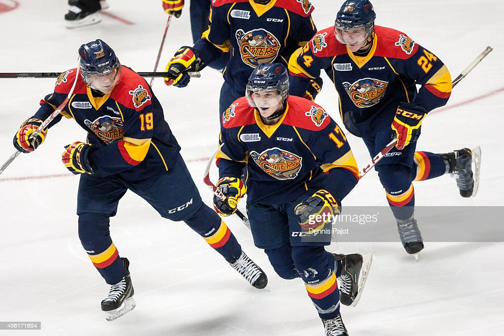 Dylan Strome #19, Taylor Raddysh #17 and Darren Raddysh #24 of the Erie Otters celebrate a goal against the Windsor Spitfires on September 26, 2014 at the WFCU Centre in Windsor, Ontario, Canada.