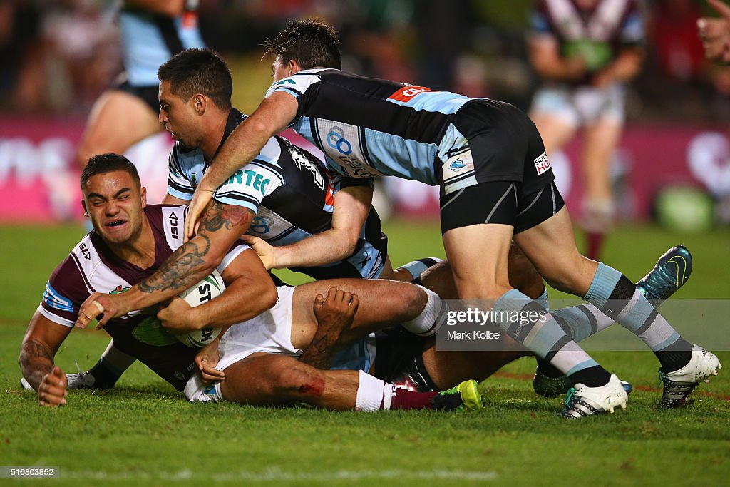 Dylan Walker of the Eagles is tackled by Gerard Beale and Chad Townsend of the Sharks during the round three NRL match between the Manly Sea Eagles and the Cronulla Sharks at Brookvale Oval on March 21, 2016 in Sydney, Australia.