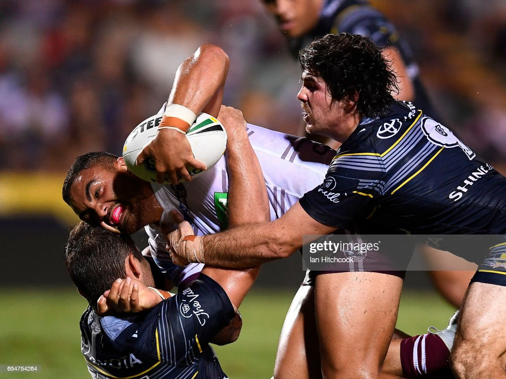 Dylan Walker of the Sea Eagles is tackled by Jake Granville and Benjamin Hampton of the Cowboys during the round three NRL match between the North Queensland Cowboys and the Manly Sea Eagles at 1300SMILES Stadium on March 18, 2017 in Townsville, Australia.