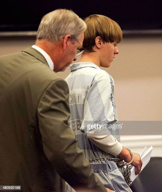 Dylann Roof is helped to his chair by chief public defender Ashley Pennington during a hearing at the Judicial Center July 16 2015 in Charleston...