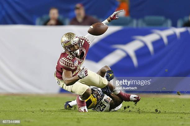 Dymonte Thomas of the Michigan Wolverines defends against Travis Rudolph of the Florida State Seminoles during the 2016 Capital One Orange Bowl at...