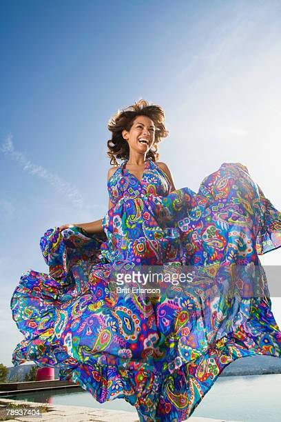 Dynamic beauty woman laughing outdoors in a colorful long summer dress.
