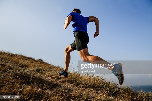 dynamic running uphill on trail male athlete runner side view : Stock Photo
