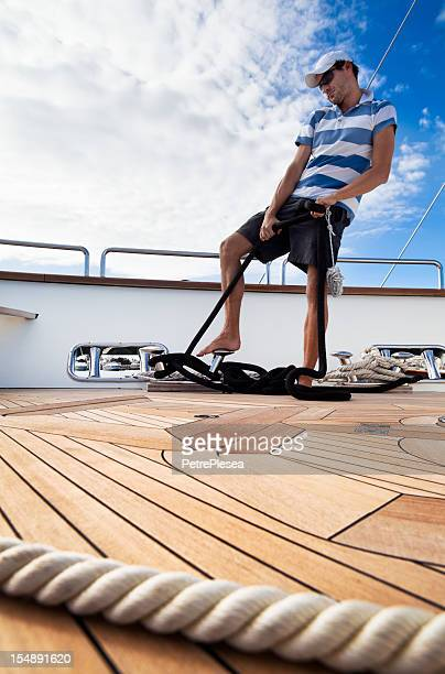 Dynamic sailor on board of the yacht tightening ropes