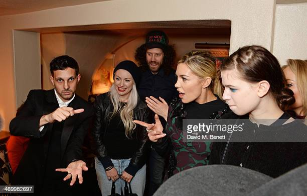 Dynamo performs a magic trick for guests including Abbey Clancy and Lily McMenamy attend the launch of LOVE special editions at George on February 17...