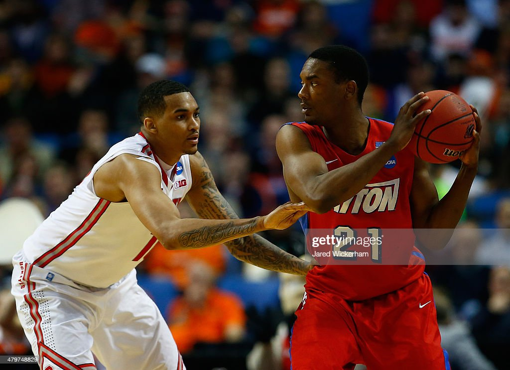 Dyshawn Pierre of the Dayton Flyers looks to pass as LaQuinton Ross of the Ohio State Buckeyes defends during the second round of the 2014 NCAA Men's...