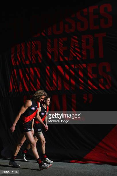 Dyson Heppell and Zach Merrett of the Bombers walk out during the round 15 AFL match between the Essendon Bombers and the Brisbane Lions at Etihad...