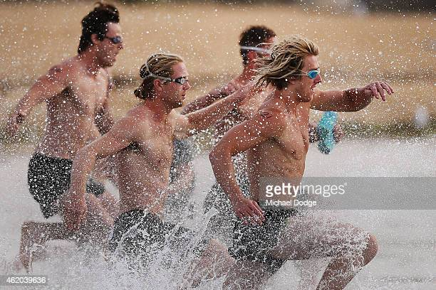 Dyson Heppell leads the start of an Essendon Bombers AFL mini triathlon training session at Williamstown Beach on January 24 2015 in Melbourne...