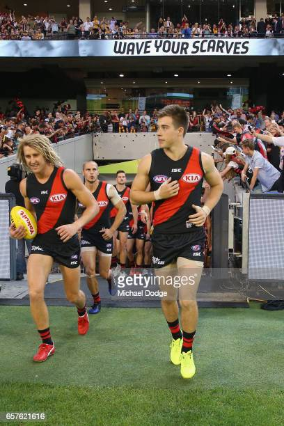 Dyson Heppell of the Bombers and Zach Merrett lead the team out during the round one AFL match between the Essendon Bombers and the Hawthorn Hawks at...