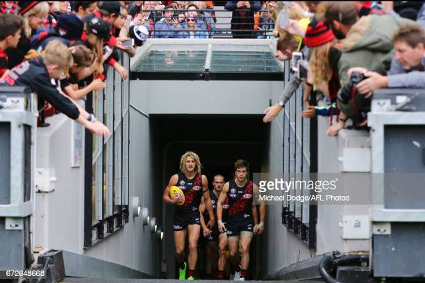 Dyson Heppell of the Bombers and Zach Merrett lead the team out during the round five AFL match between the Essendon Bombers and the Collingwood...