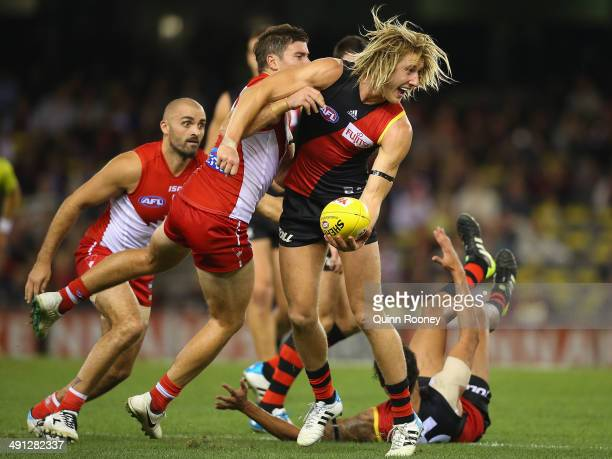Dyson Heppell of the Bombers handballs whilst being tackled by Craig Bird of the Swans during the round nine AFL match between the Essendon Bombers...