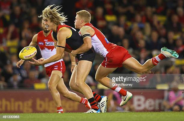 Dyson Heppell of the Bombers handballs whilst being tackled by Daniel Hannebery of the Swans during the round nine AFL match between the Essendon...