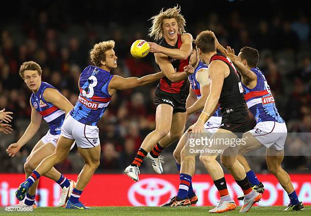 Dyson Heppell of the Bombers handballs whilst being tackled by Mitch Wallis of the Bulldogs during the round 18 AFL match between the Essendon...