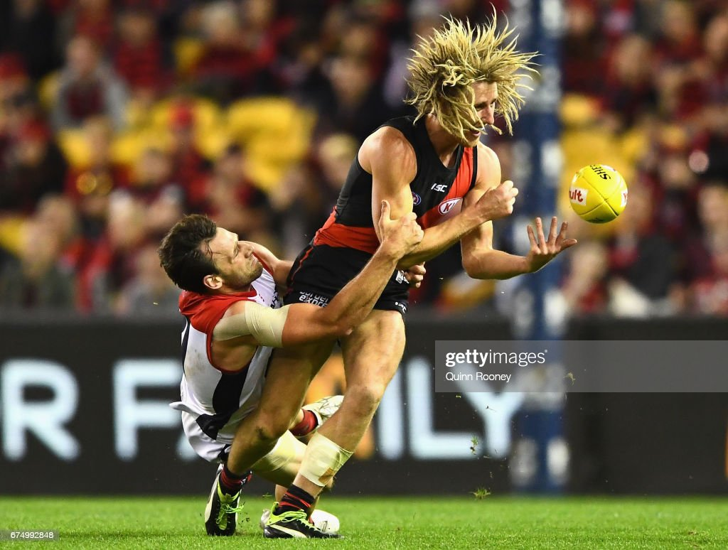 Dyson Heppell of the Bombers handballs whilst being tackled by Cameron Pedersen of the Demons during the round six AFL match between the Essendon Bombers and the Melbourne Demons at Etihad Stadium on April 30, 2017 in Melbourne, Australia.