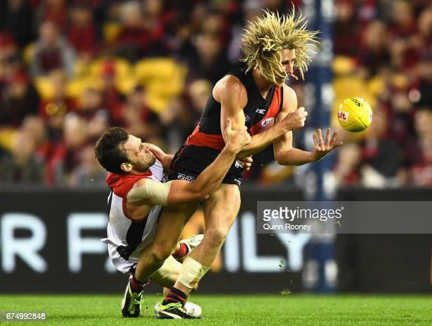 Dyson Heppell of the Bombers handballs whilst being tackled by Cameron Pedersen of the Demons during the round six AFL match between the Essendon...