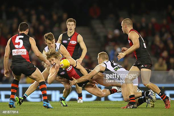 Dyson Heppell of the Bombers handballs whilst being tackled by Robbie Gray and Andrew Moore of the Power during the round 17 AFL match between the...