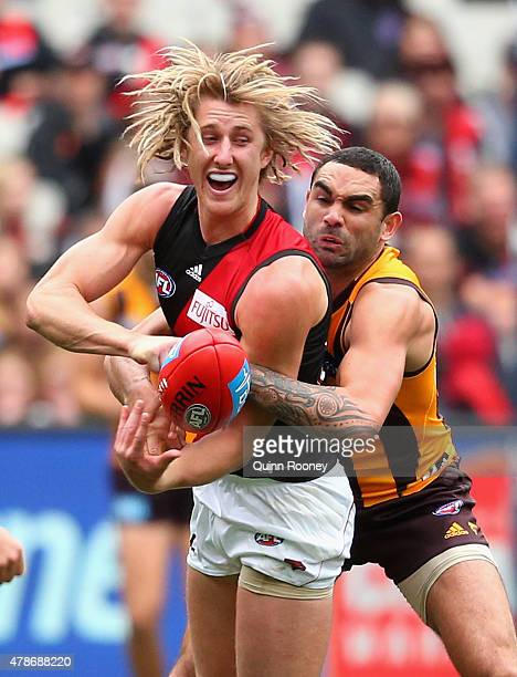 Dyson Heppell of the Bombers handballs whilst being tackled by Shaun Burgoyne of the Hawks during the round 13 AFL match between the Hawthorn Hawks...