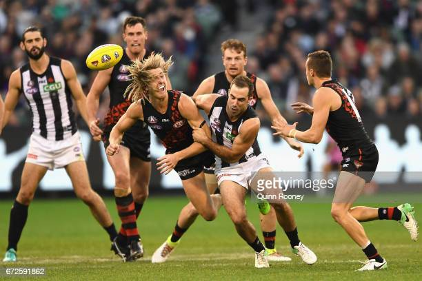 Dyson Heppell of the Bombers handballs whilst being tackled by Steele Sidebottom of the Magpies during the round five AFL match between the Essendon...