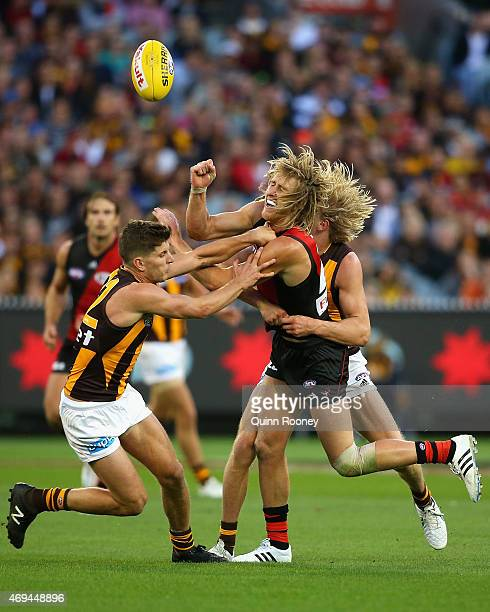 Dyson Heppell of the Bombers handballs whilst being tackled by Will Langford of the hawks during the round two AFL match between the Essendon Bombers...