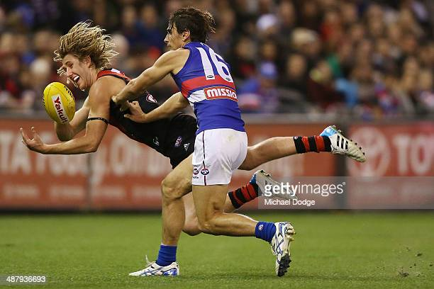 Dyson Heppell of the Bombers handpasses the ball away from Ryan Griffin of the Bulldogs during the round seven AFL match between the Essendon Bombers...