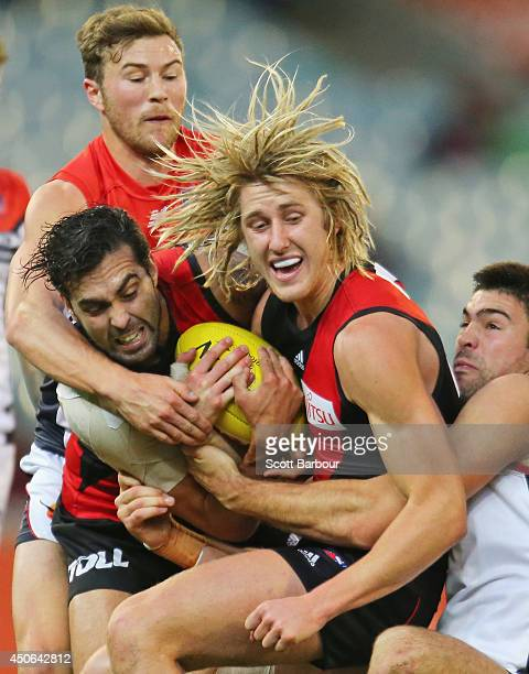 Dyson Heppell of the Bombers is tackled during the round 13 AFL match between the Essendon Bombers and the Melbourne Demons at the Melbourne Cricket...