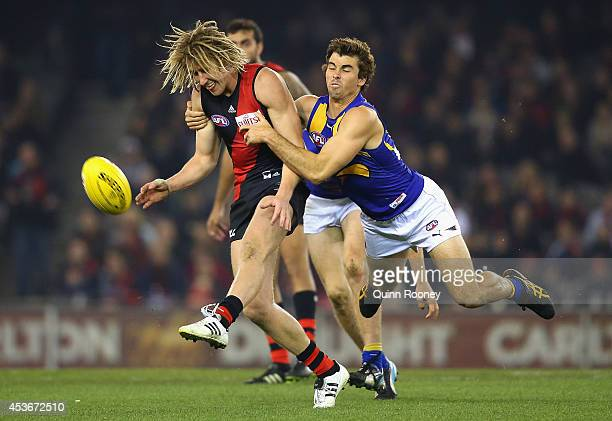 Dyson Heppell of the Bombers kicks whilst being tackled by Jamie Cripps of the Eagles during the round 21 AFL match between the Essendon Bombers and...