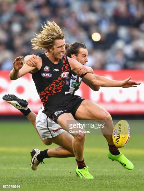 Dyson Heppell of the Bombers kicks whilst being tackled Tim Broomhead of the Magpies during the round five AFL match between the Essendon Bombers and...
