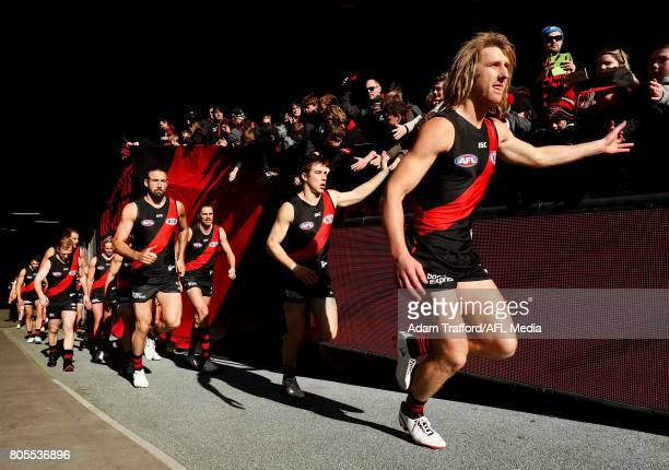 Dyson Heppell of the Bombers leads the team onto the field during the 2017 AFL round 15 match between the Essendon Bombers and the Brisbane Lions at...